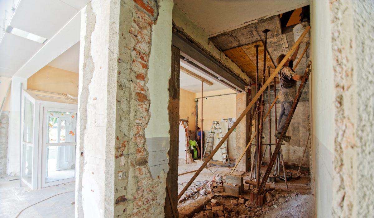 Sanierungsarbeiten mit Mann auf Leiter